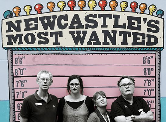 Museum staff infront of Newcastle's most wanted sign